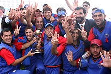 Afghanistan celebrate with the trophy after their two-wicket victory in the Final against Jersey.